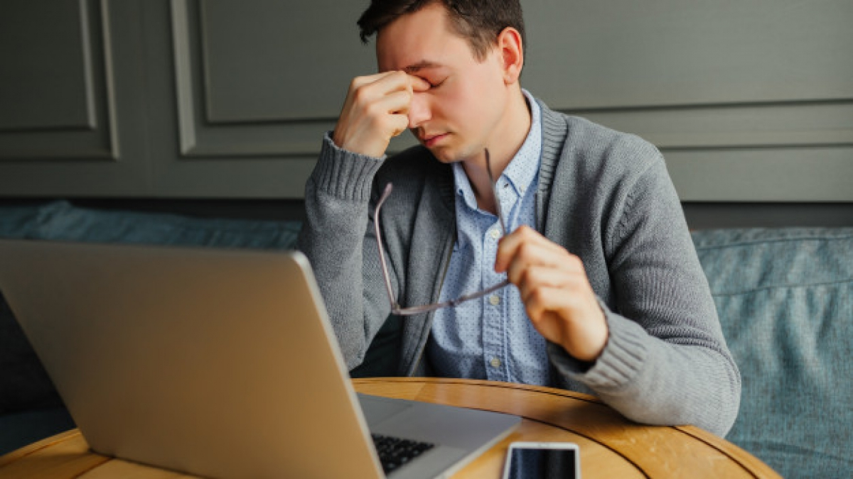 frustrated-young-man-massaging-his-nose-keeping-eyes-closed-while-working_8353-5961