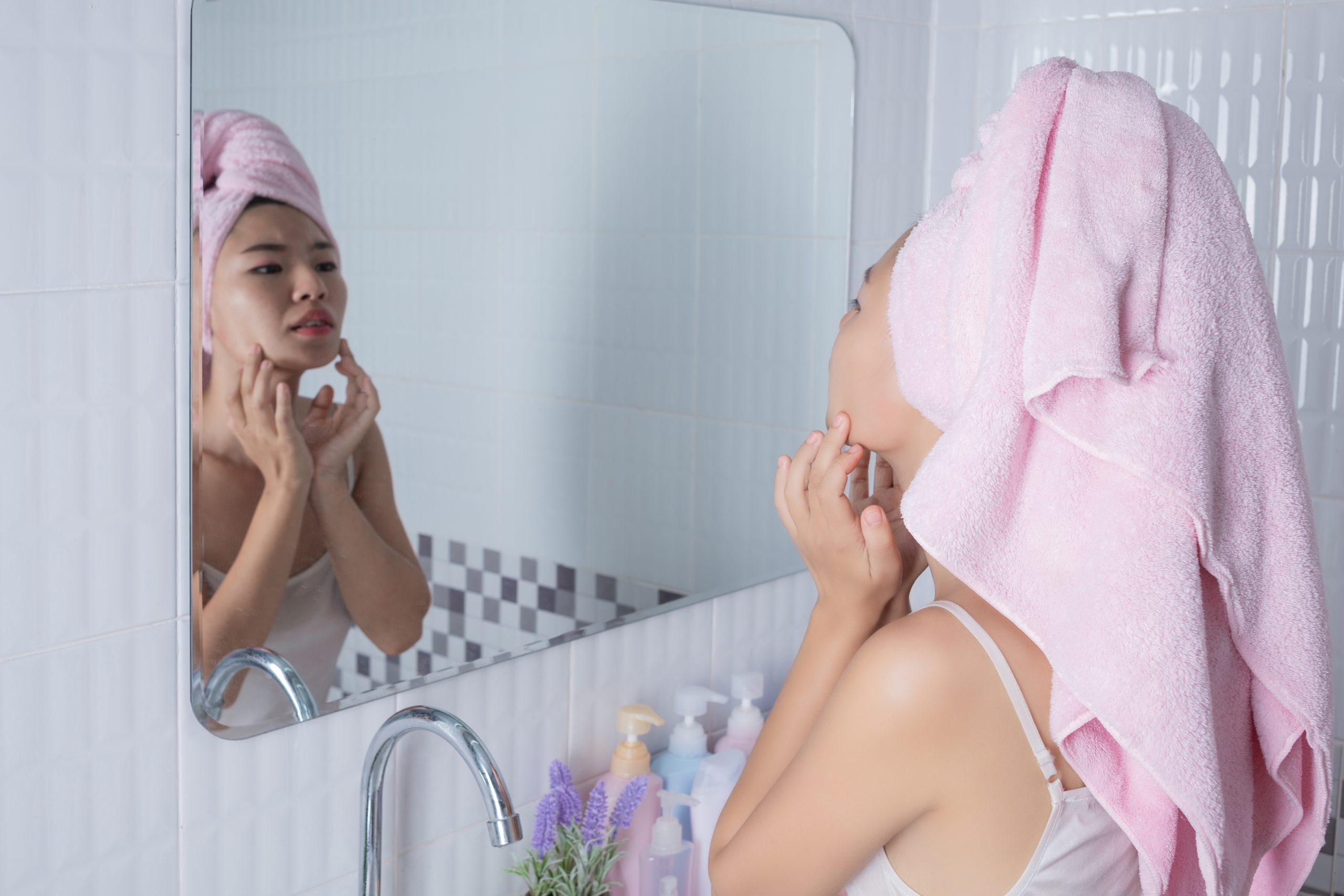 Asian girl squeezes acne.