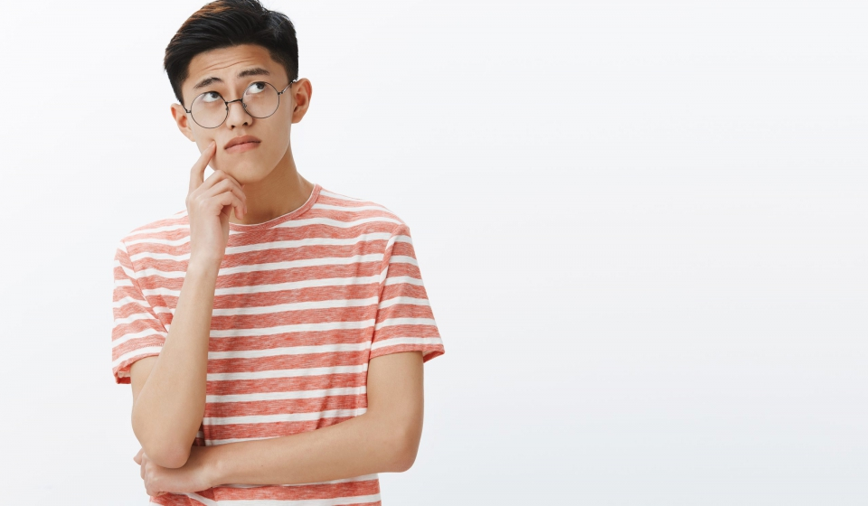 Smart asian guy solving puzzle in mind looking thoughtful and relaxed at upper right corner, thinking, making assumptions touching cheek while making up plan or decision, posing in glasses. Body language concept