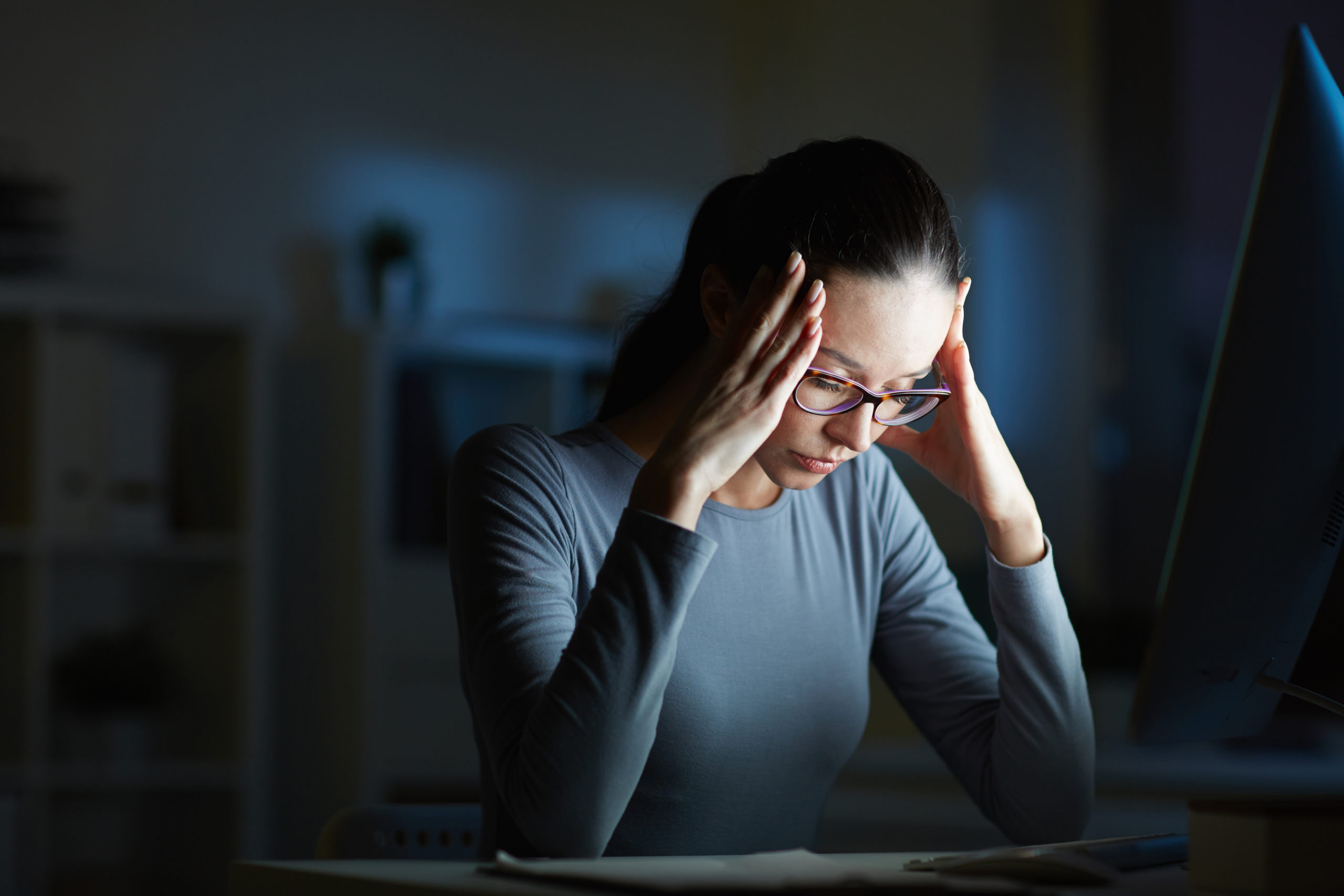 Young businesswoman with headache touching her head while sitting in front of computer monitor by her workplace at night